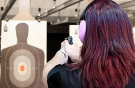 Woman Shooting Target at Indoor Range